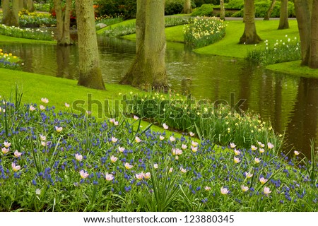 Colorful river and flowerbed  in dutch garden 'Keukenhof', Netherlands - stock photo