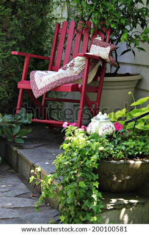 Colorful rocking chair in a cottage garden setting. - stock photo