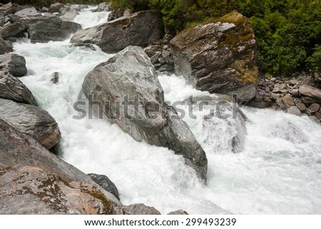 Colorful Rocks in White Water - New Zealand, Mt Aspiring National Park - stock photo