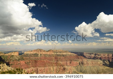 Colorful rocky canyon walls, blue skies with white clouds. - stock photo