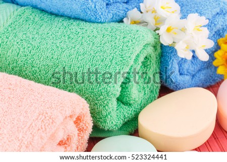 Colorful rolled towels with flowers and soaps closeup picture.