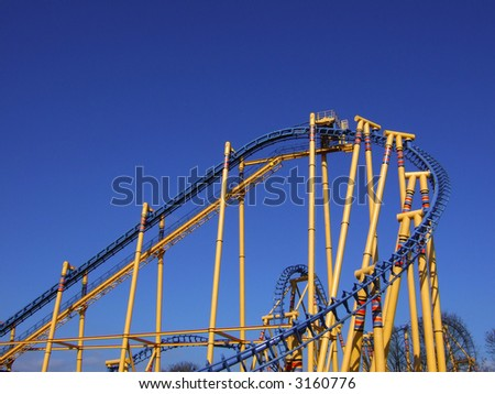 Colorful roller coaster against a blue sky - stock photo