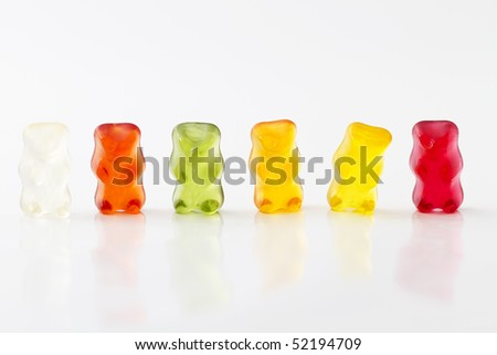 colorful row of jelly bears on white background - stock photo