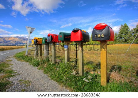 Colorful row of post boxes by a roadside - stock photo