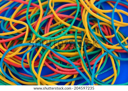 Colorful rubber bands on blue background close-up