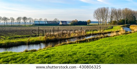 Colorful rural landscape with a meandering stream with yellowed reeds at the banks on a sunny day in the fall season.