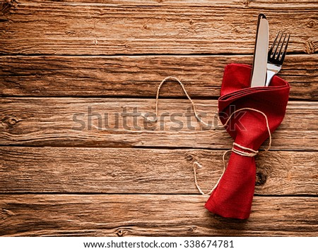 Colorful rustic festive place setting with a knife and fork tied in a vivid red festive Christmas napkin with string resting on a wooden table with copyspace - stock photo