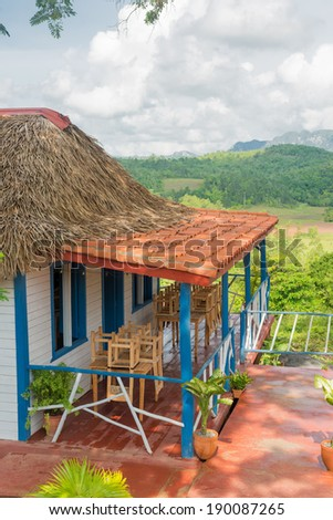 Colorful rustic wooden house with a terrace overlooking the Vinales Valley in Cuba - stock photo