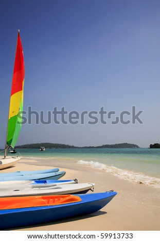 Colorful sailboat and some rental kayaks along an exotic beach in southern Thailand - stock photo