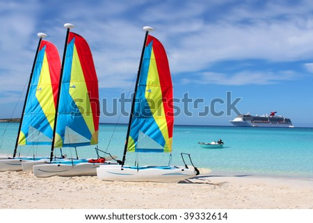 Colorful sailboats and motorboat, on a tropical beach at Half Moon Cay in the Bahamas with cruise ship in background on a tropical beach at Half Moon Cay in the Bahamas - stock photo