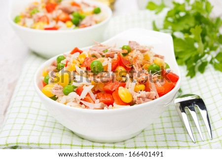 colorful salad with corn, green peas, rice, red pepper and tuna in a bowl, close-up - stock photo