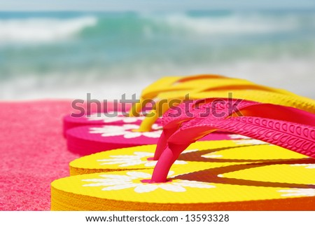 Colorful sandals on beach towel next to ocean - stock photo