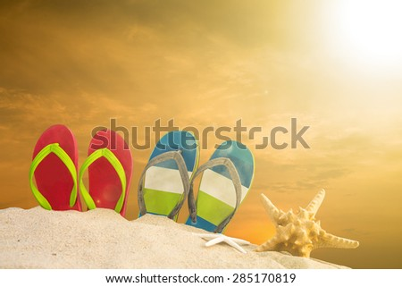 Colorful sandals on beach with summer concept.