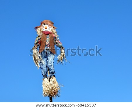Colorful Scarecrow Against Clear Blue Sky - stock photo