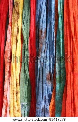 Colorful Scarves on sale at a market.  They come in blue, red, green, yellow and pink.