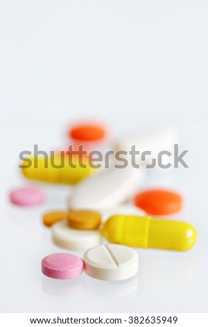 colorful scattered tablets and capsules on white background