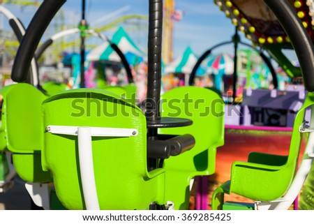 Colorful scene in a Texas amusement park featuring green chairs in the foreground