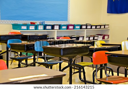 colorful school desks in an elementary classroom - stock photo