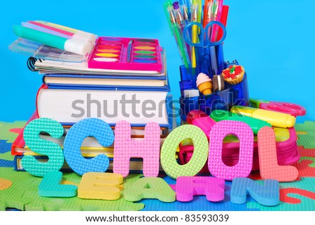 colorful school equipment against blue background - stock photo