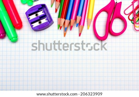 Colorful school supplies border over graphing paper  - stock photo