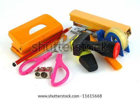 Colorful school tools of scissors, punch, pencil, ball-pen, rubber stamp, sharpener and other useful secretary items on a desk isolated on white background