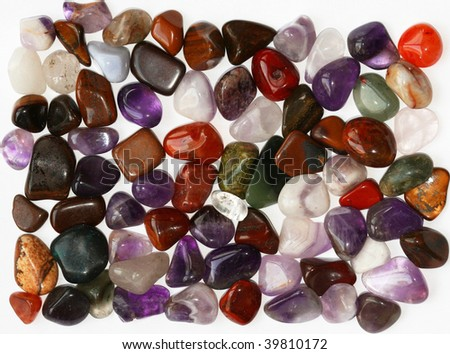 Colorful semiprecious stones on white background - stock photo