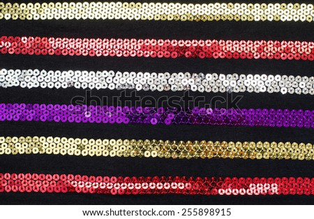 Colorful sequins striped background. Sparkly red, gold, silver, purple stripes pattern on black fabric. - stock photo