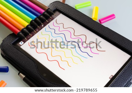 Colorful set of maker pens with squiggly lines drawn by each one on a sheet of white paper to show the vibrant color palette in the colors of the rainbow or spectrum - stock photo