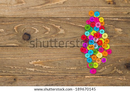 Colorful sewing buttons on a wooden background with copy space.  - stock photo