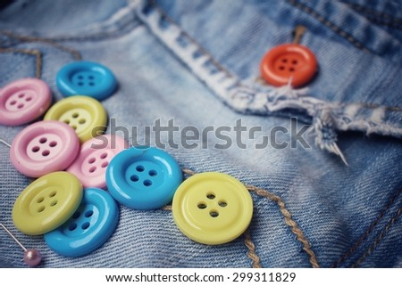 Colorful sewing buttons on jeans