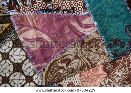 colorful sewn patchwork batik quilt fabric in brown, pink, blue, and white with zigzag stitching - stock photo