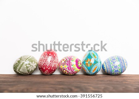 colorful shiny easter eggs on wooden table - stock photo