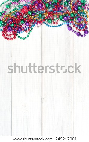Colorful  Shiny Mardi Gras Beads on Rustic Painted White Board Background with room or space for copy, text, your words.  Vertical  - stock photo