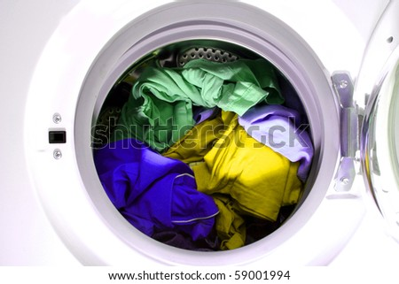 Colorful shirt and trousers in a white laundry. - stock photo