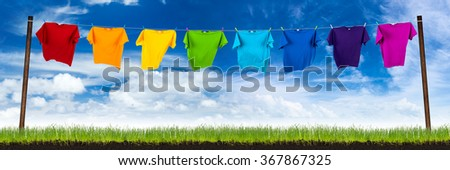 colorful shirts on washing line on green meadow
