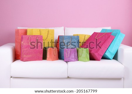 Colorful shopping bags on sofa, on color wall background