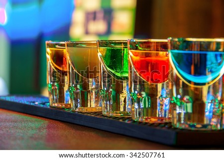Colorful shot drinks in nightclub in summer - stock photo