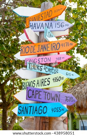 colorful sign points the way to the different destinations in the world. - stock photo