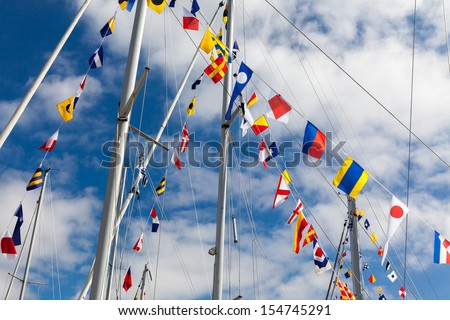 Colorful signal flags on a sailing boat in sunshine - stock photo