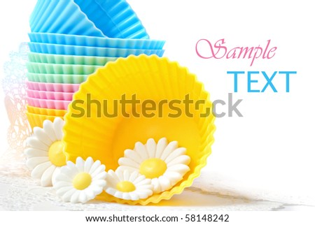 Colorful silicone baking cups with daisies made of cake icing on white background with copy space.  Macro with shallow dof. - stock photo