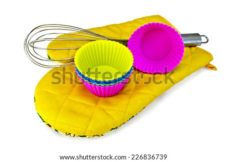 Colorful silicone molds for cupcakes, mixer on yellow cloth potholder isolated on white background  - stock photo