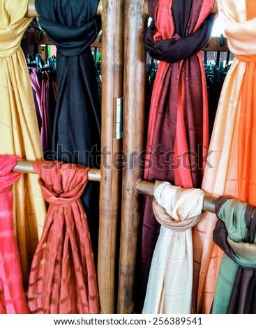 Colorful silk shawls in the Thai souvenir shop. - stock photo