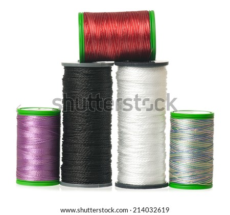 Colorful silk threads on a coils isolated on white background close-up - stock photo