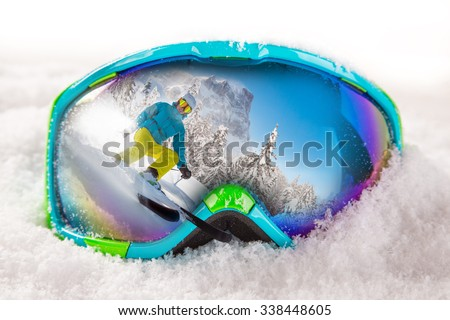 Colorful ski glasses with skier on snow. Winter ski theme. - stock photo