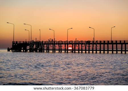 Colorful sky during sunset seen from behind Thavorn beach pier in Phuket thailand - stock photo