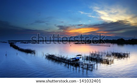 Colorful sky with fish farms - stock photo