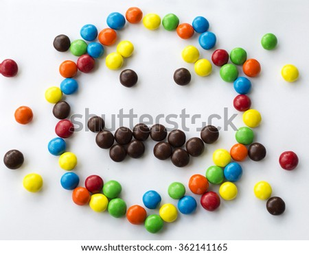 colorful smiley kind emotional candy face on white background made of round candies wearing mustache - stock photo