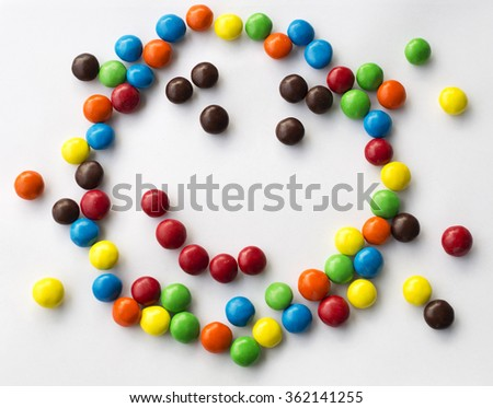 colorful smiley, kind, happy emotional candy face on white background made of round candies for children games looks like Kapitoshka - stock photo