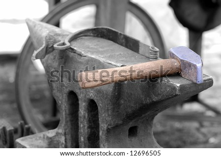 Colorful smith hammer on a black and white anvil - stock photo