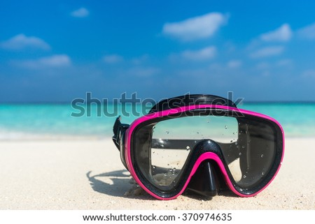 Colorful snorkel mask by the sea, remote tropical beaches. Travel and vacation concept